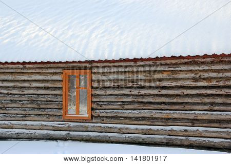 Log wall, window and snow-covered roof of the village house