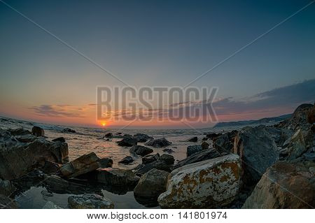 Sunset over the coast with stones. Fish-eye lens