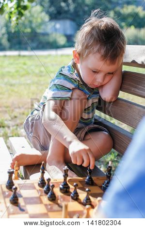 baby sitting on a bench and playing chess. boy sitting with his feet on the bench and is going to make a chess move