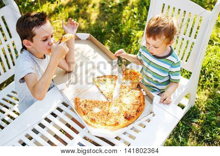 kids eating pizza at a table outside. two boys eating pizza takeaway. top view