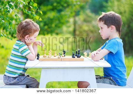 two boys playing chess outdoors. older brother and younger brother sitting opposite each other and playing chess