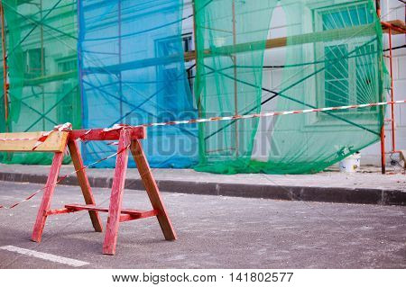 repair work on the building. fencing on the road near a building with scaffolding. closed passage