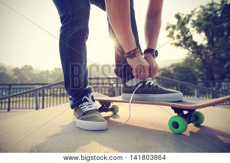 one young skateboarder tying shoelace on skateboard