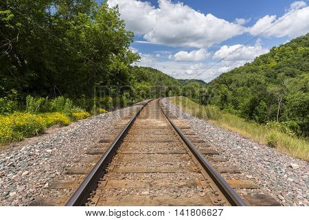 A railroad track traveling through scenic hills.