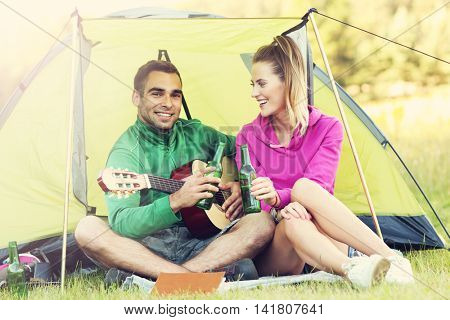 Picture showing couple camping in forest and playing guitar