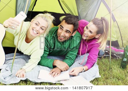 Picture showing group of friends camping in forest and taking selfie