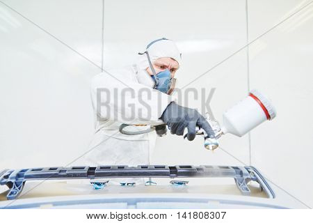 repairman painter in chamber painting automobile car bumper
