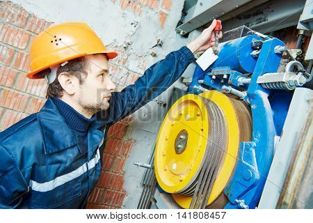 machinist worker adjusting elevator mechanism of lift