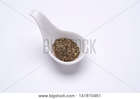 Monotone dry Basil 1 tablespoon in a white spoon on the white background