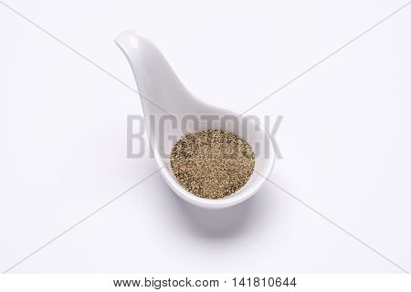 Monotone ground black pepper 1 tablespoon in a white spoon on the white background