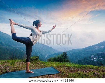 Woman doing yoga asana Natarajasana - Lord of the dance pose outdoors at waterfall in Himalayas