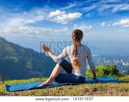 Hatha yoga outdoors - sporty fit woman doing yoga asana Parivrtta Marichyasana (or ardha matsyendrasana) -  seated spinal twist outdoors in mountains in the  morning