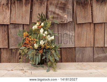 Holiday flower bouquet inside a gourd vase with red berries, green leaves and sprigs, and white roses on a rustic wood farm house background.