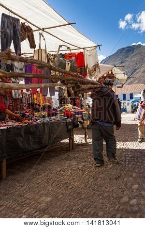 Peruvian Man Carrying Poles In Pisac
