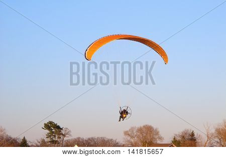 A man soars above houses and trees in a powered paraglider a contraption consisting of a wing harness and motor.