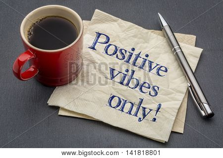 Positive vibes only - handwriting on a napkin with cup of coffee against gray slate stone background