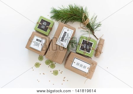 Kraft And Green Christmas Presents. The Branches Of The Christmas Tree. Gifts Tied With Jute Rope.