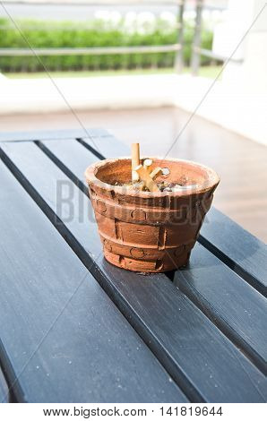 Full ashtray make by pottery on wood table
