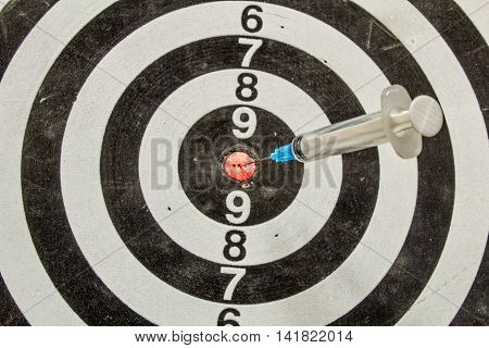 Plastic Medical Syringe Stuck In A Dartboard Closeup