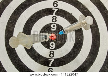 Two Medical Syringes Stuck In A Dartboard Closeup
