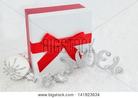 Christmas gift box with red bow, silver noel sign, white snowflake bauble and pine cone decorations on snow background.