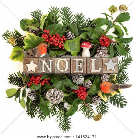 Old wooden noel block sign with holly and red berries, ivy, fly agaric mushroom and robin decorations with snow covered pine cones and fir over white background.