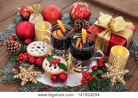 Christmas still life with food and drink of mulled wine, mince pies, gold snowflake and red bauble decorations, gift box, candles, holly and snow covered fir on oak background.