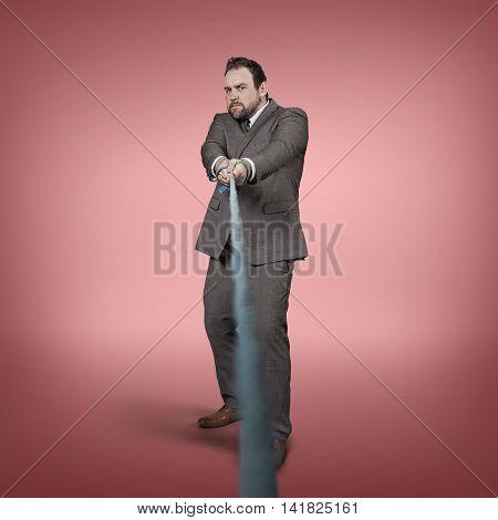 Businessman pulling rope at office - studio shot