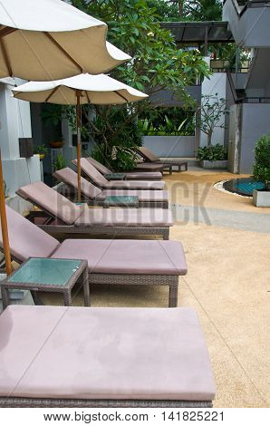 chaise lounges beside swimming pool in hotel