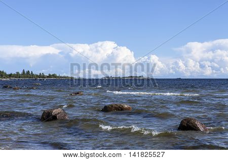 Summer day by the sea. Some stones, rocks and clouds in the background.
