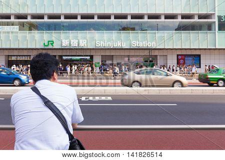 TOKYO JAPAN - 18 JULY 2016 - Asian man waits across the stree from JR Shinjuku station in Tokyo Japan on July 18 2016