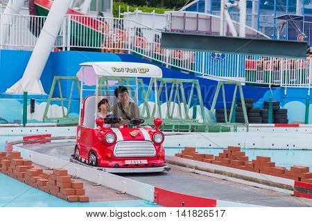 TOKYO JAPAN - 19 JULY 2016 - Asian father and daughter ride together at Furi Furi Grand Prix ride at Tokyo Dome City theme park in Tokyo Japan on July 19 2016.