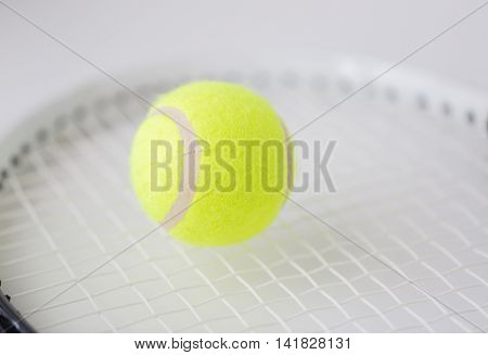 sport, fitness, sports equipment and objects concept - close up of tennis racket with ball