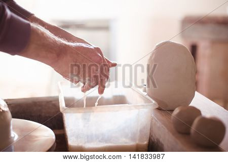 Close-up of male potter washing hands after working on pottery wheel in pottery workshop
