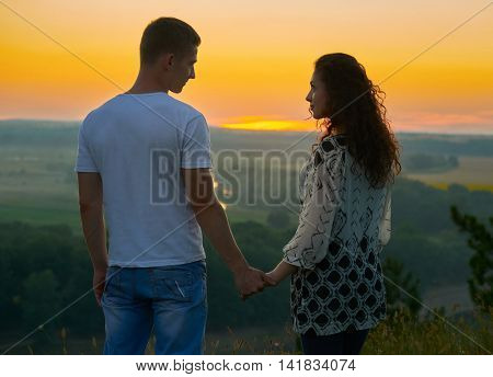 romantic couple looking into the distance at sunset on outdoor, beautiful landscape and bright yellow sky, love tenderness concept, young adult people