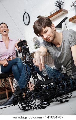 Happy young couple changing light bulb in chandelier at home.