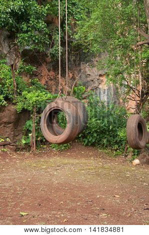 old tire swing hanging in park, handmade toy in Thailand