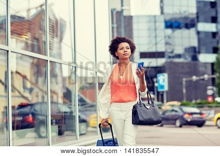 travel, business trip, people and technology concept - young african american woman with travel bag and smartphone on city street