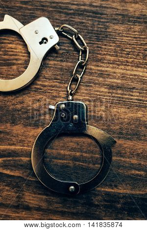 Police handcuffs on investigator detective's work desk concept of law and crime.