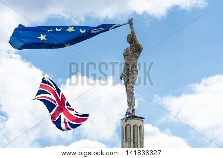 Proposed referendum on United Kingdom membership of the European Union antique stone statue holds a European flag in hand including the British Flag.