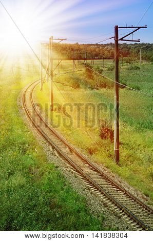 Curved railroad track, lit by the sun. Against the backdrop of forests and mountains.