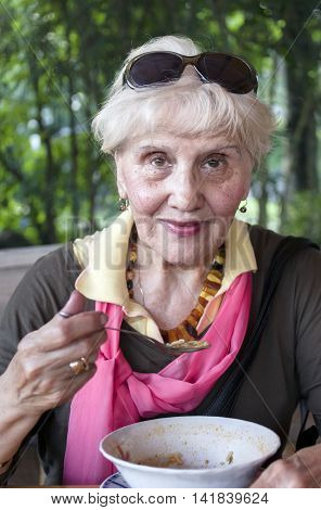 A smiling aged woman having a soup posing outdoors vertical portrait