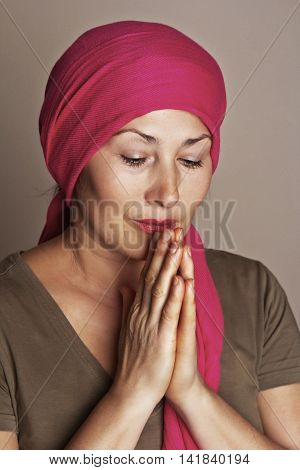 Middle-aged asian woman close up in a deep prayer