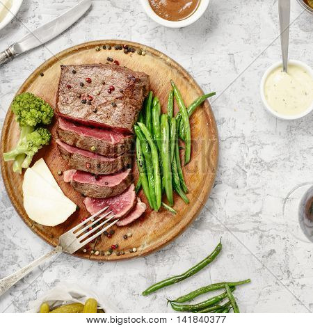Steak with side dish of French beans on wooden board close up on rough white surface top view