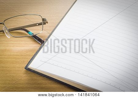 Eyeglasses And Open Note Book With Blank Page