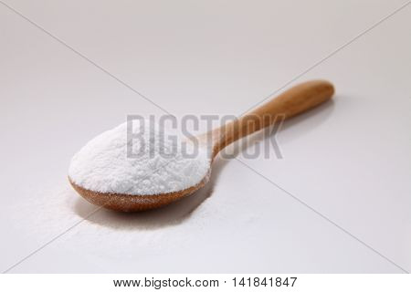 wooden spoon full of baking soda on the white background