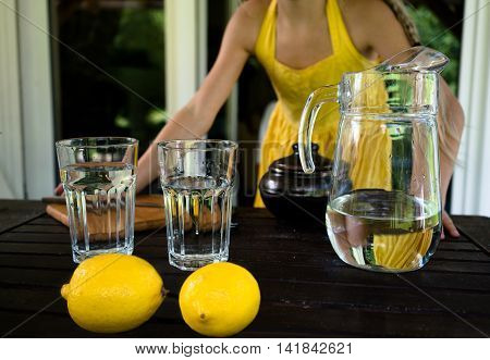 lemons and glass jug with glasses in the summer on a background of a window