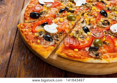 Delicious italian vegetarian pizza with tomatoes, mushrooms, peppers, corn and black olives - thin pastry crust at wooden table background, one piece cut