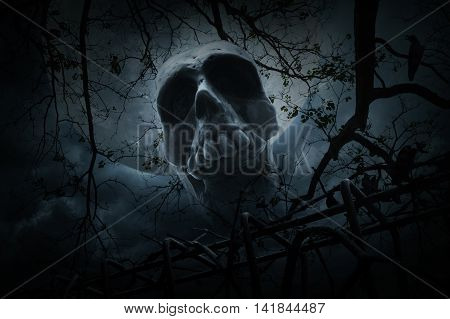 Human skull with old fence over dead tree crow moon and cloudy sky Spooky background Halloween concept