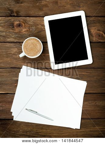 Tablet PC, coffee and papers on wooden table. Empty device screen with copy space, white sheets and cappuccino cup top view